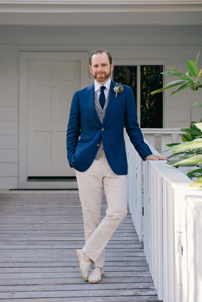 Groom stands in unique & trendy menswear.